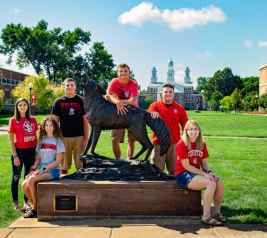 Six of the 2018 Coyote Legacy Scholarship recipients pose with the Legacy statue on USD's campus.