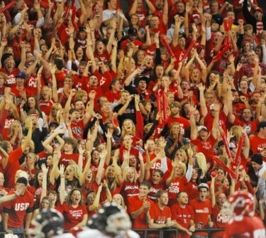 Coyote students cheer in the stands at a football game.