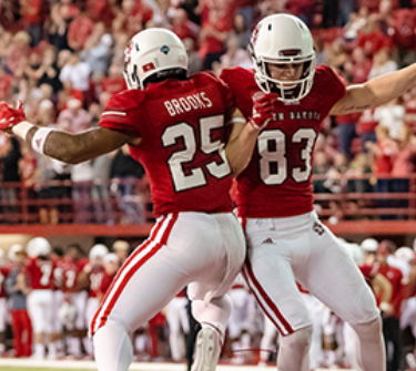 Two Coyote football players celebrate during a game at the DakotaDome.