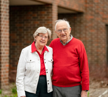 Truman and Beverly Schwartz stand together on USD's campus.